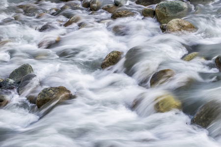 downstream: White silky water flowing downstream over the rocks and boulders