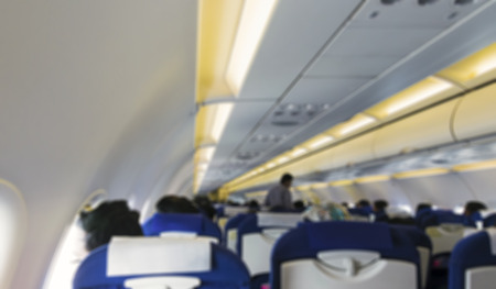 onboard: Blurred image of airplane interior  cabin with passengers onboard