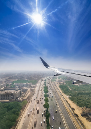 View through the window of a passenger plane flying above Delhi Gurgaon highway, taken just a minute before landing at the New Delhi Airport T3 terminal