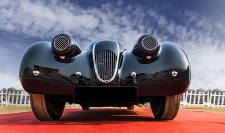 Vooraanzicht van de lage hoek van een onbekende oldtimer retro vintage sportwagen onder blauwe bewolkte hemel. De voorkant en chroomrooster van klassieke schoonheid ziet er stevig maar elegant en aantrekkelijk uit.