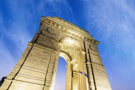 A wide angle closeup view of the India Gate (formerly known as the All India War Memorial) at New Delhi and blue cloudy sky in background.