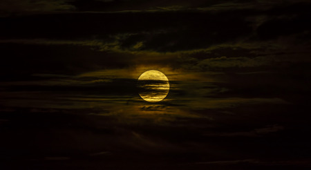 surrounded: The beautiful full moon surrounded by the silky clouds at night Stock Photo