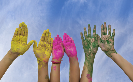 Hands  Palms of young people covered in pink, yellow, green Holi festival colors isolated