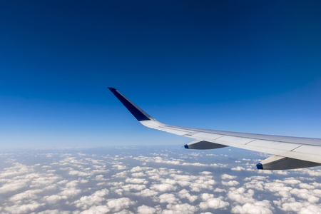 Wing of a flying passenger airplane above clouds in the sky Stock Photo