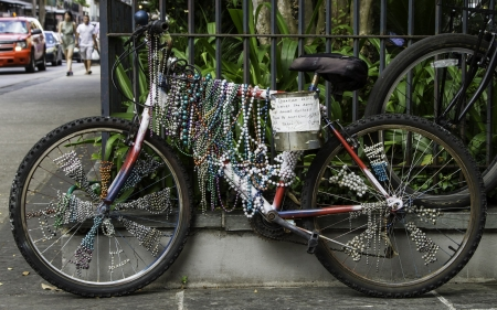 velocipede: An old bike covered in beads parked at the French Quarter in New Orleans