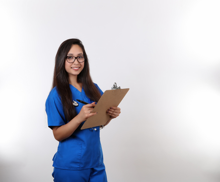 vitals: A young hispanic nurse in blue scrubs wearing glasses.