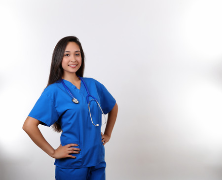 vitals: A young hispanic nurse in blue scrubs. Stock Photo