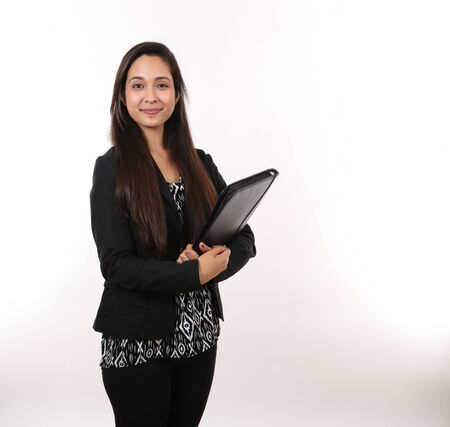 An attractive young executive assistant holds her portfolio and smiles.
