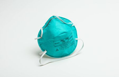 Houston, TX - April 12, 2020: A closeup of an isolated turquoise 3M N95 protective respirator face mask. Reklamní fotografie