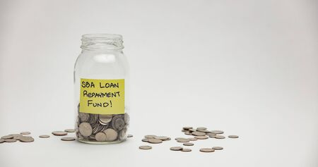 A glass jar holds many quarters, dimes and nickels for an SBA loan repayment.