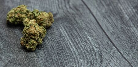 Three high quality bright green marijuana buds on a wooden table. Orange color and many crystals on buds.