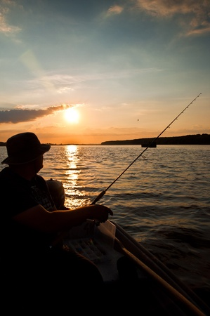 Fisherman on evening who fishing on boat Stock Photo