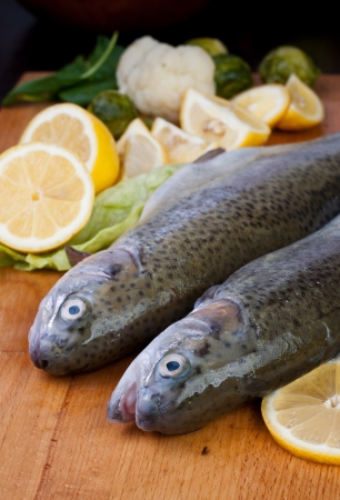 fresh strict trout in lemons and vegetables on the board Stock Photo