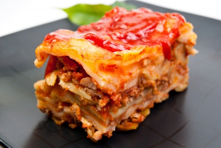 Portin of lasagne on dish photo