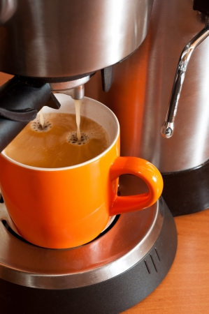 percolator: Orange coffee cup in the percolator from hot esppresso Stock Photo