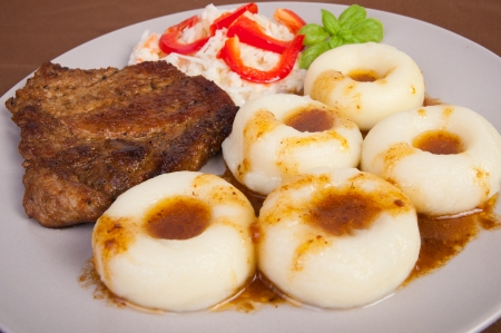 Polish silesia's potato dumplings with the roasted meat and the salad photo