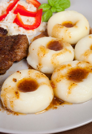 Polish silesia s potato dumplings with the roasted meat and the salad photo