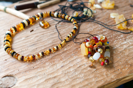 Hand-made ​​necklace using simple tools of ancient amber and colored glass  - in the background tools  Stock Photo
