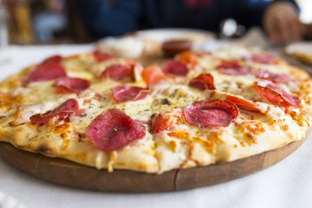 unsliced: Pizza on desk - focus selected, natural light