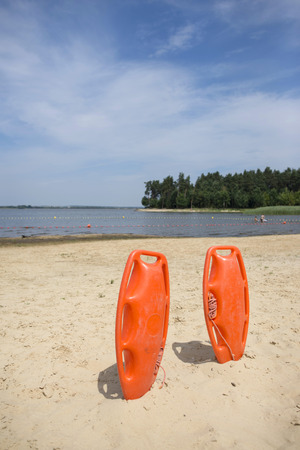 lifeguard equipment in sand on a water Stock Photo