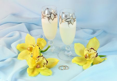 Orchids, champagne and wedding rings are on a silk fabric photo