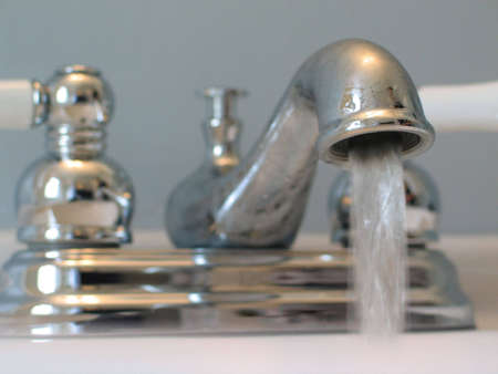 Close-up of old-fashioned looking chrome and porcelain faucet, with water running out of it. Stock Photo