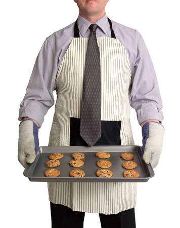 Image of a man against a white background, wearing a kitchen apron and oven mitts over business attire. He is holding a cookie sheet full of freshly-baked chocolate chip cookies in front of him.