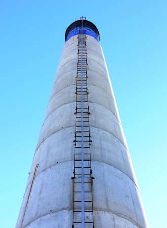 Shot of a blue, white and black chimney with a ladder, from the bottom up, against a blue sky. Stock Photo