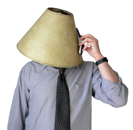 Businessman with a lampshade on his head, trying to talk on his cell phone.
