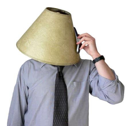 abatjour: Uomo d'affari con un paralume sulla sua testa, cercando di parlare a suo telefono cellulare.