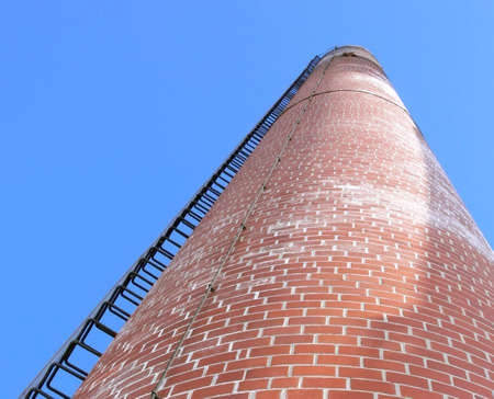 Photo of a chimney stack with a ladder running up the side. The photo is taken from the bottom looking up, with a blue sky in the background. Photo was taken in Selkirk, Manitoba, Canada.