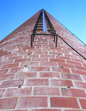 Photo of a chimney stack with a ladder running up the middle. The photo is taken from the bottom looking up, with a blue sky in the background. Photo was taken in Selkirk, Manitoba, Canada.