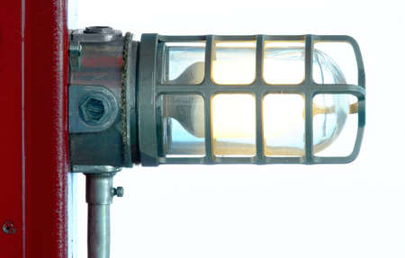 Industrial-looking light fixture attached to a red post.