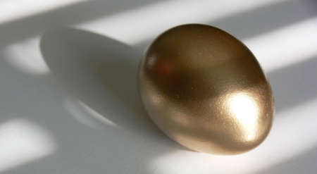 Golden egg on a white tabletop, with patterns of light and shadow laying across both. Stock Photo