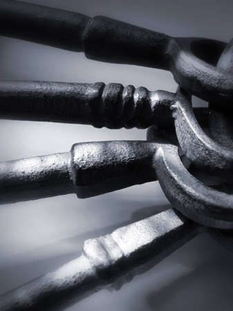 Stack of four oversized, cast iron antique keys on a ring. Entire image was given a grey/blue, pewter-like hue. Stock Photo