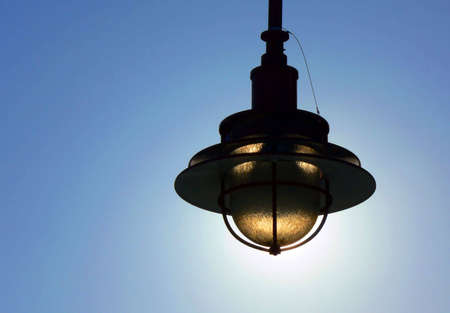 Exterior light fixture silhouetted against the sun.