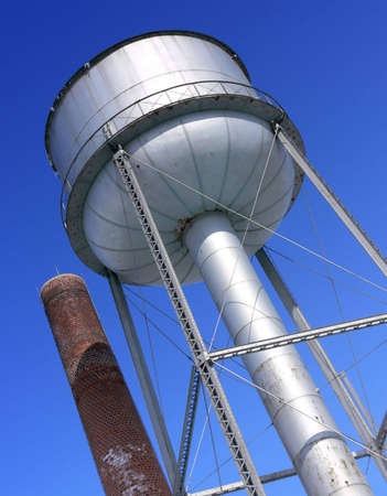 Photo of a water tower next to a brick chimney stack, against a blue sky. Photo was taken in Selkirk, Manitoba, Canada. Stock Photo