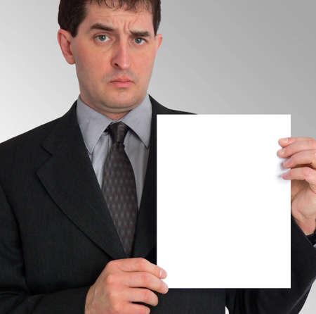 hoja en blanco: Imagen de un hombre de negocios que sostiene una hoja en blanco del papel a su izquierda, contra un fondo gris del gradiente. Foto de archivo
