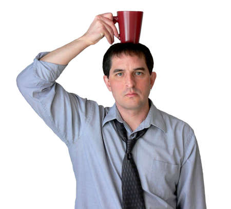 Businessman with tie undone, balancing his coffee mug on his head.