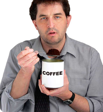 Tired, dishevelled business man eating coffee from the can. Stock Photo - 417491