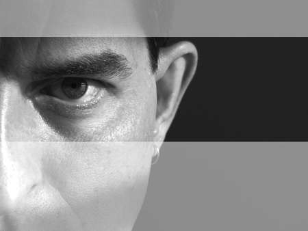 engaging: Black and white closeup of the left side of a mans face. Man is looking serious and intense and maybe angry. There are lighter bands going across the top and bottom of the image, drawing the viewers eye to the models eye.Taken in my bathroom with sunli