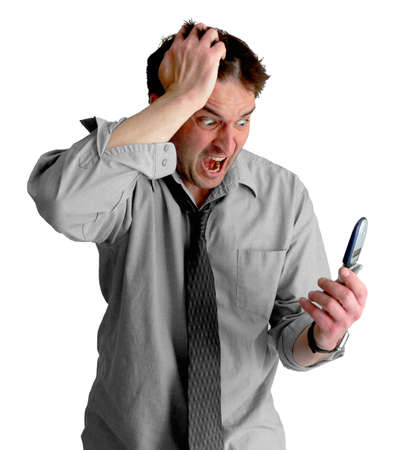 Angry, freaked-out business man pulling his hair while yelling at a cell phone.