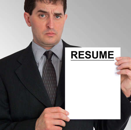 Image of a businessman holding a resume to his left, against a grey gradient background. Stock Photo - 417485