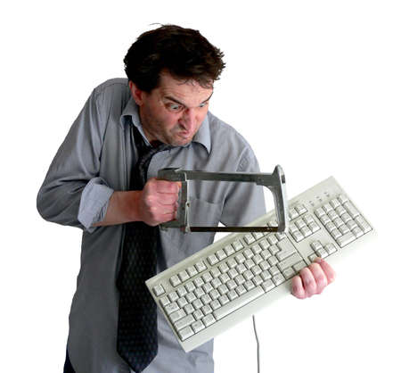 sawing: Tired, freaked-out business man sawing a keyboard in half with a hacksaw. Stock Photo