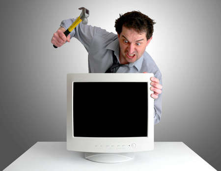 smash: Tired, freaked-out business man preparing to smash a computer monitor with a hammer.