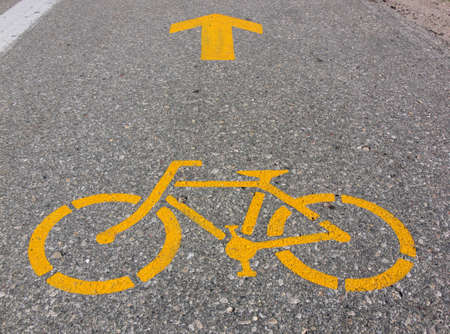 Bycicle and arrow symbols painted in yellow on highway shoulder.