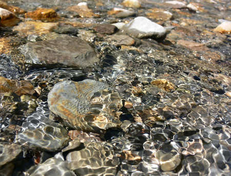 Clear water running over colourful rocks and pebbles in a stream.