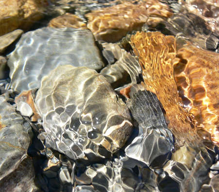 Close-up of clear water running over colourful rocks and pebbles in a stream.