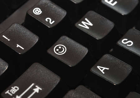 Close-up of a computer keyboard, with a smiley face on one of the keys.