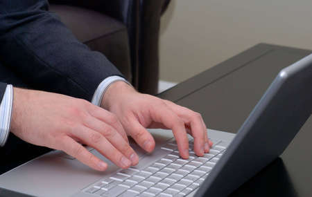 Businessmans hands on the keyboard of a silver laptop computer.